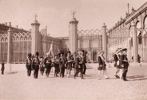 Группа высших государственных чинов - участников церемонии перенесения императорских регалий - направляется из Оружейной палаты к Большому Кремлевскому дворцу в сопровождении дворцовых гренадер.