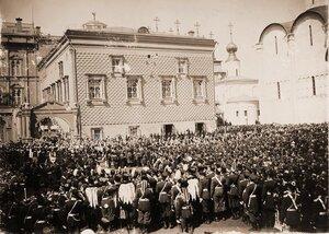 Нижние чины шефских частей и зрители на Соборной площади Кремля наблюдают шествиеих императорских величеств под балдахином от Красного крыльца Грановитой палаты к Успенскому собору в день торжественной коронации.
