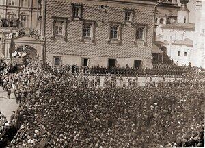 Взвод лейб-гвардии Кавалергардского полка у нижних ступеней Красного крыльца Грановитой палаты и генерал-адъютанты, несущие балдахин (слева от кавалергардов), следуют за высшими государственными чинами, направляющими