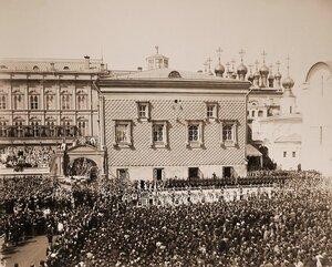 Император Николай II и императрица Александра Федоровна, шествующие под балдахином, в сопровождении свиты направляются в Успенский собор; по ступеням Красного крыльца спускается взвод лейб-гвардии Кавалергардского по