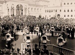 Церемониймейстеры (с жезлами) и герольды проходят мимо Чудова монастыря в Кремле в день торжественной коронации; справа на втором плане - вид части фасада Малого Николаевского дворца.