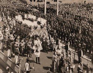 Торжественное шествие императора Николая II (под балдахином) в сопровождении свиты по окончании церемонии коронации в Успенском соборе Кремля; справа (в нижнем углу снимка) - церемониймейстеры (с жезлами), далее - ве