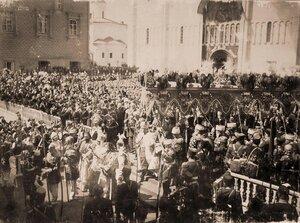 Император Николай II (под балдахином) в сопровождении свиты выходит из южных дверей Успенского собора на Соборную площадь Кремля по окончании церемонии торжественной коронации; перед императором - митрополит Санкт-Пе