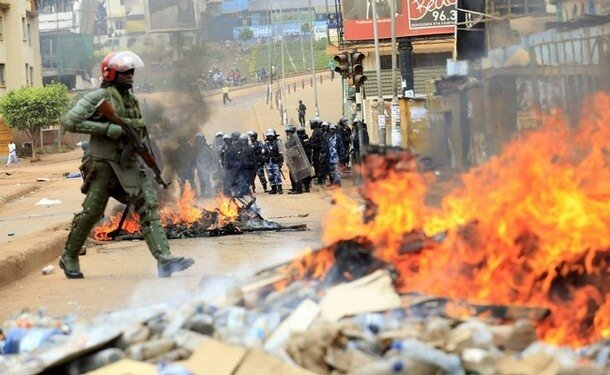 A Ugandan military police officer walks past a barricaded road in Kampala