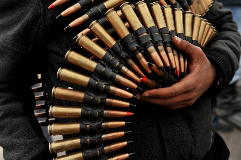 A Libyan rebel fighter holds belts of am