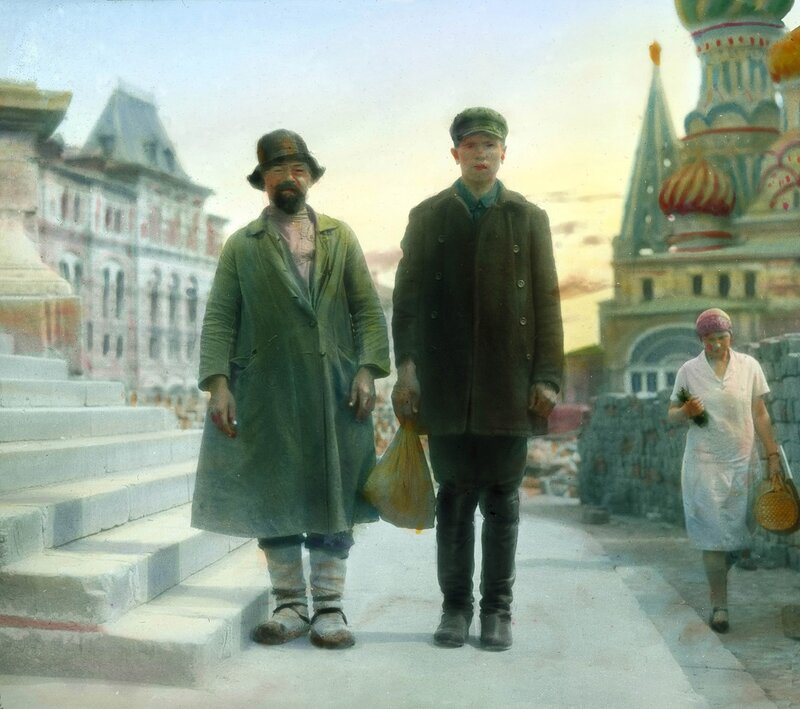 Moscow: portrait of two poorly-dressed men near St. Basil's Cathedral