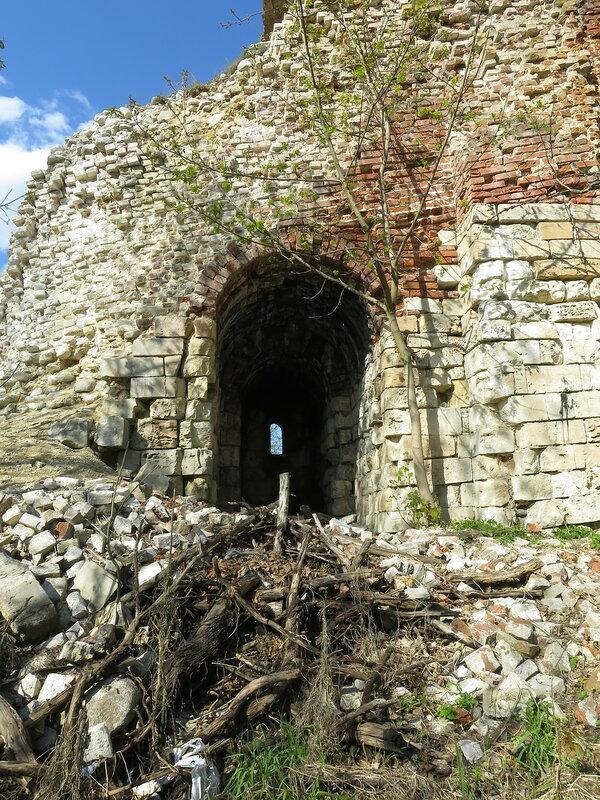 Сохранившаяся бойница подошвенного боя в руинированном фрагменте стены