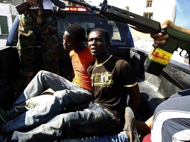 Men accused of being a Libyan leader  Muammar Gaddafi loyalist mercenaries sit in a rebel vehicle in Tripoli