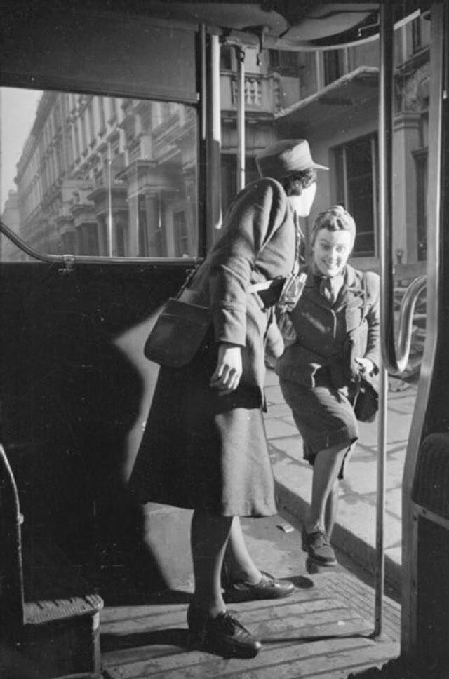 21. Кондуктор помогает Оливии запрыгнуть в автобус по пути на работу. Фотография, скорей всего, сделана на Фулхэм Роуд