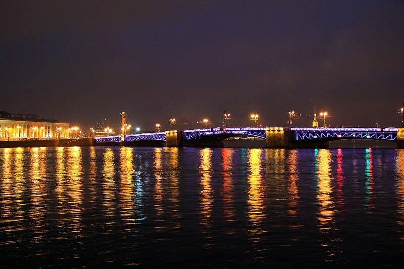 Отражение цветных огней в реке Неве и ночная подсветка Дворцового моста в Санкт-Петербурге.
