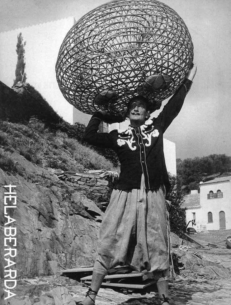 1955. Сальвадор Дали держит на голове рыбацкую ловушку как Геркулес глобус