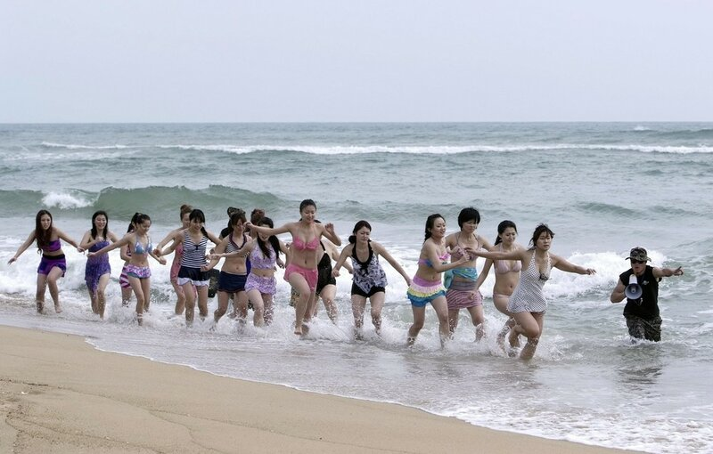 Trainees dressed in swimsuits run through waves under the direction of a trainer from Tianjiao Special Guard/Security Consultant Ltd. Co. during a training session in Sanya