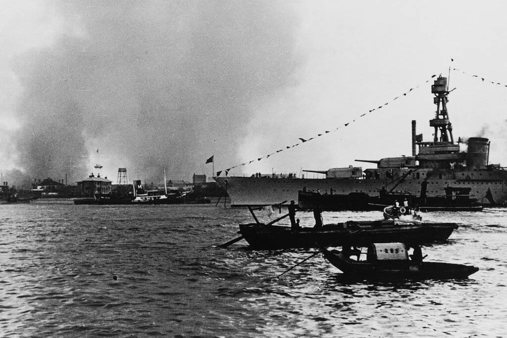USS AUGUSTA (CA-31) Moored to a British warship buoy astern (upstream) with both forward anchors down. Off Pootung Point, Shanghai, China. Smoke from burning mills set afire by Japanese shelling and bombing. Circa November 1937 (Armistice Day).