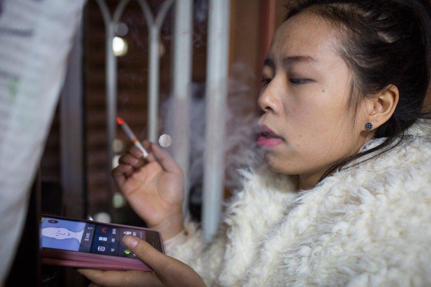 Кьёнг-ок курит у себя на балконе. Сейчас она учится в третьем классе старшей школы, а начала курить