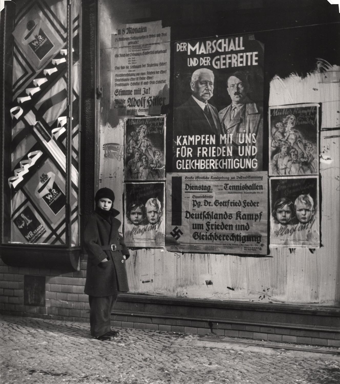 1933. Дочь Вишниака Мара позирует перед избирательным плакатом для Гинденбурга и Гитлера, который гласит «Ммаршал и ефрейтор сражаются вместе с нами за мир и равные права», Вильмерсдорф, Берлин