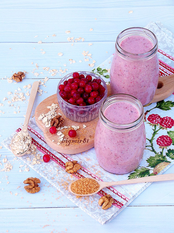 healthy smoothies from berries, oatmeal, nuts and brown sugar on a light wooden background.