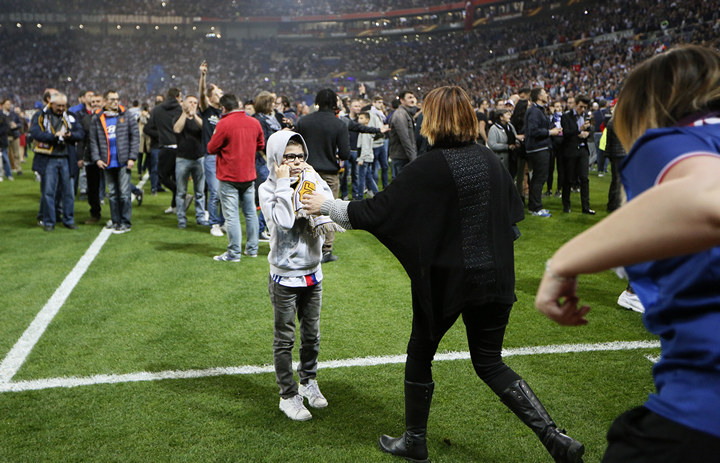 Lyon fans on the pitch as fans clash in the stands