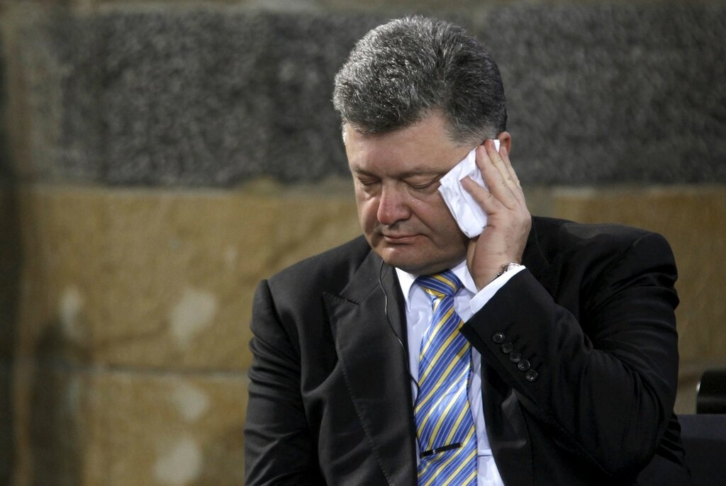 Ukraine's President Poroshenko wipes his face during the ceremony of the Charlemagne Prize 2015 in Aachen