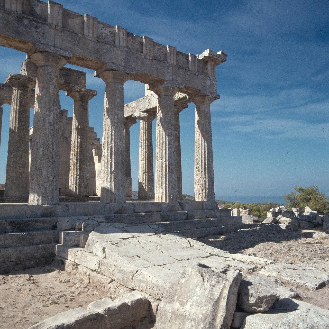 17. В пропорциях храма чувствуются архаические черты. Хотя колонны довольно стройны, но антаблемент тяжел по отношению к ним. На снимке: Часть восточного фронтона и соединение крыла храма с алтарями