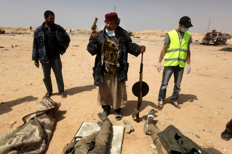 A Libyan rebel gestures over dead bodies