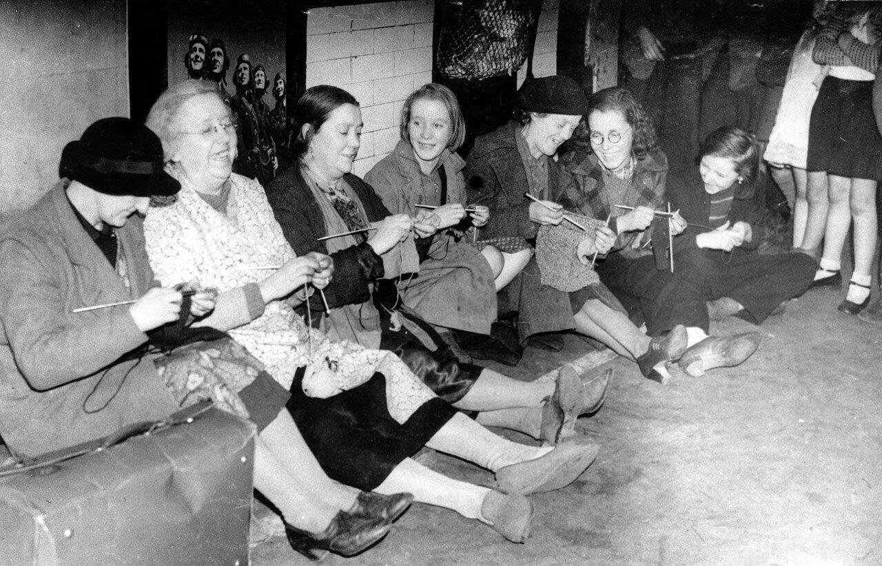 1940. Женщины вяжут и беседуют на станции метро во время немецкой мощной бомбардировки Лондона