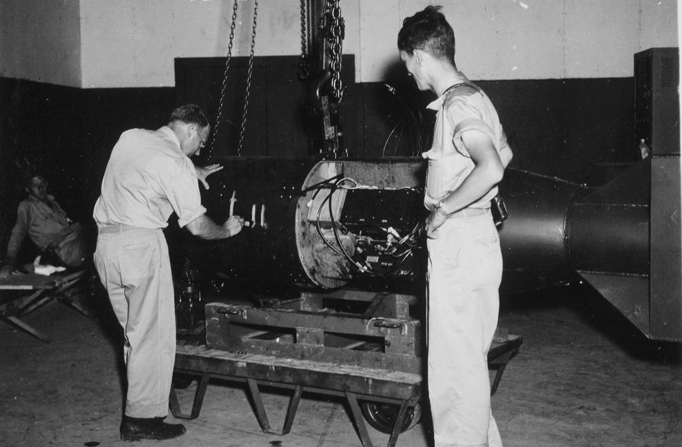 5. Командир А.Ф. Бирч (слева) нумерует бомбу под кодовым названием «Малыш» перед погрузкой ее на тре