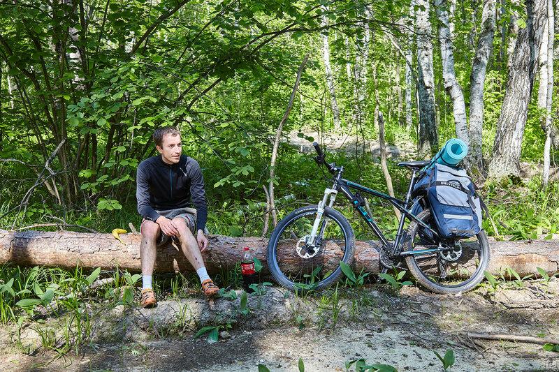 Два мужика копают в лесу и велосипедистка