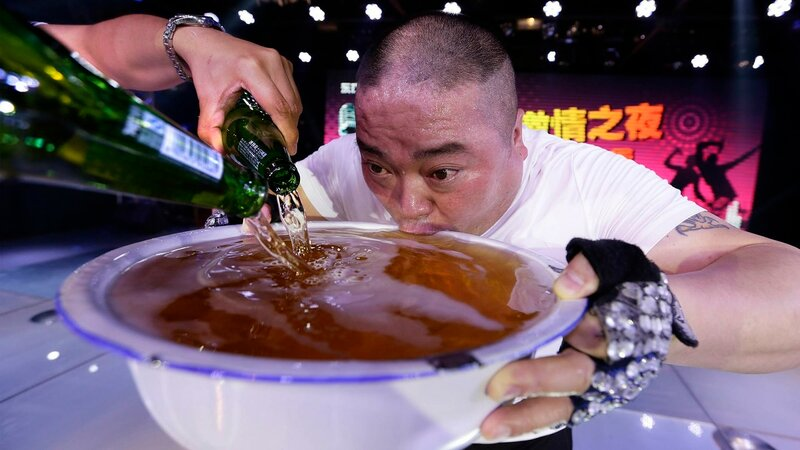 A singer drinks from a huge bowl of beer on-stage as he pays tribute to the customers after performing at an entertainment club in Beijing