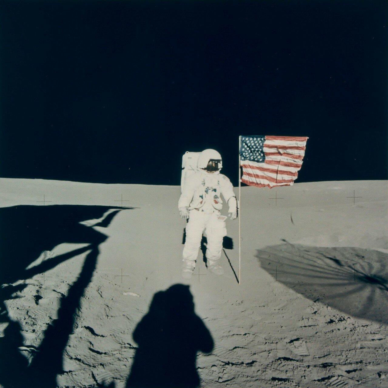 В 115 часов 49 минут полётного времени астронавтов попросили подойти к флагу, после чего им передали послание президента Никсона. На снимке Эдгар Митчелл с американским флагом