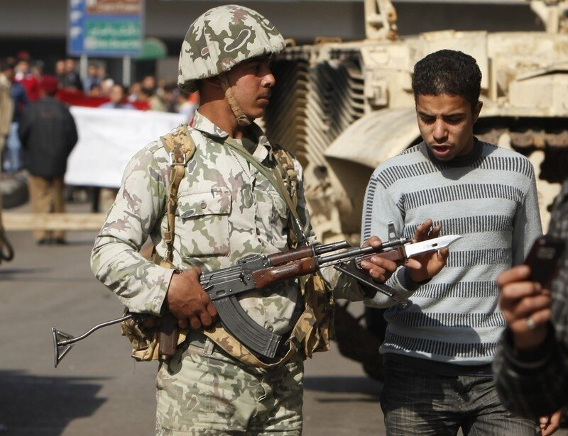 A protester touches the weapon of a soldier in downtown Cairo