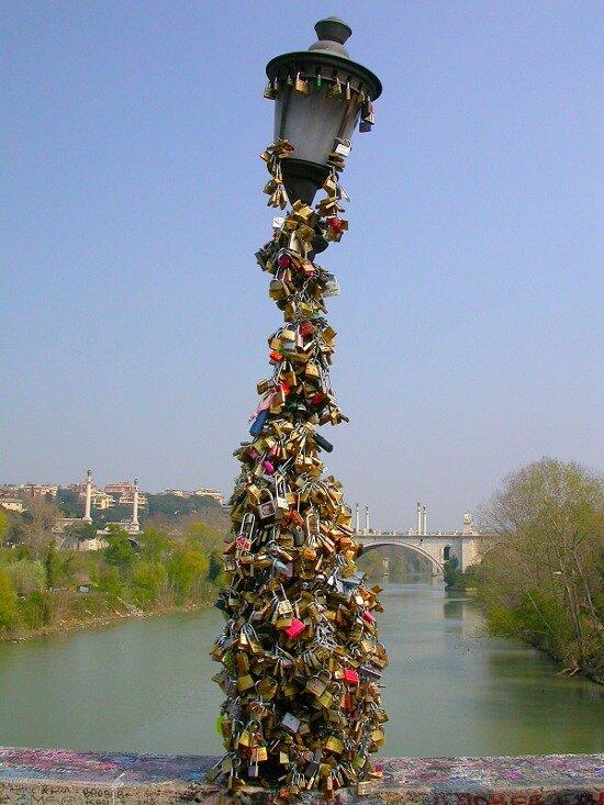 знаменитый фонарный столб с висячими замками из Мильвийского моста в Риме, Италия.