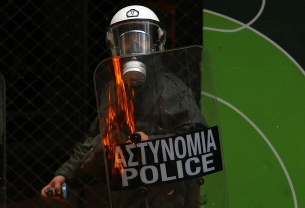 Fire is reflected on the shield of a policeman armed with a tear-gas canister during clashes in central Athens