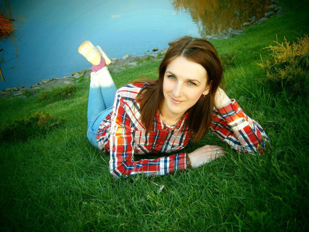 Юная девушка шатенка на берегу реки в джинсах
