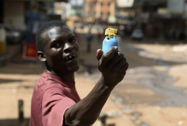 A man holds an empty teargas canister, which was fired at rioters, during demonstrations in Kampala