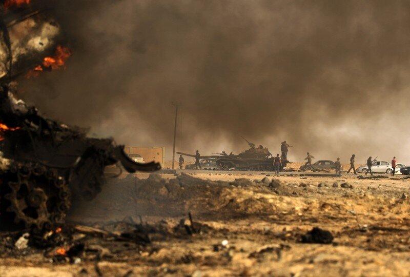 Libyan rebels gather next to burning wre