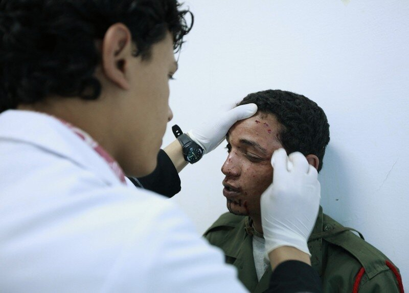 A doctor treats a wounded rebel fighter at a hospital in Ajdabiyah