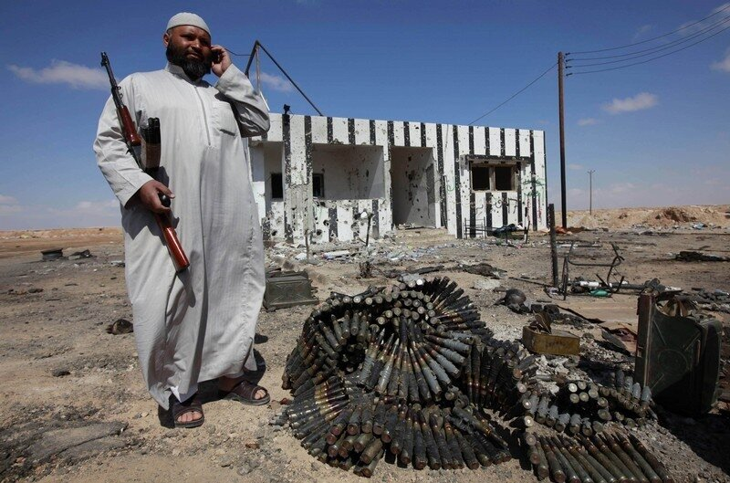 A rebel talks on his mobile phone next to a pile of anti-aircraft ammunition at a checkpoint on the west of Ajdabiyah