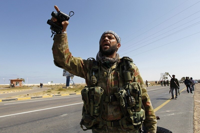 A rebel with a pair of binoculars gestures during a fight with troops loyal to Muammar Gaddafi outside Brega in eastern Libya