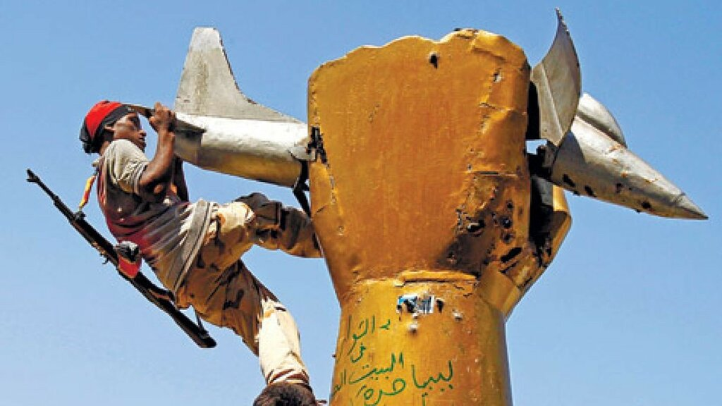A rebel climbing on the sculpture of a fist with an airplane − symbolizing American attacks on Libya in 1986.jpg