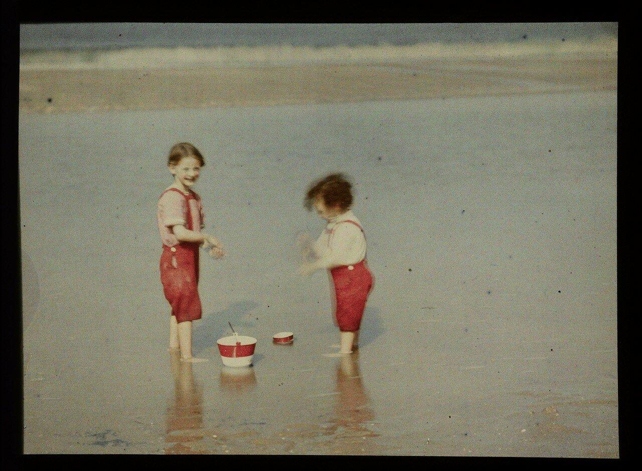 1904. Двое детей играют на пляже в Северном море