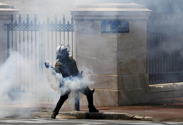 A policeman throws a teargas canister during clashes with protesters in Athens