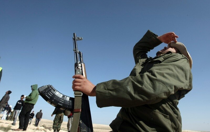 A Libyan rebel watches planes near Brega
