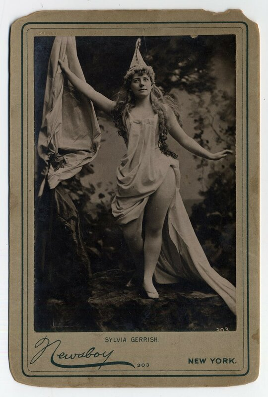 1890 Sylvia Gerrish with draped dress and pointed hat in woods.