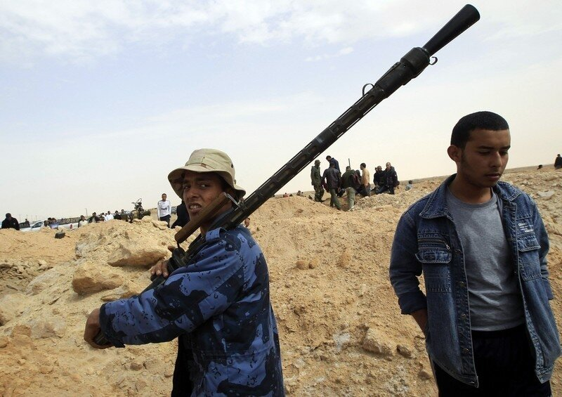 A rebel holds a gun on the outskirts of Ajdabiya, on the road leading to Brega