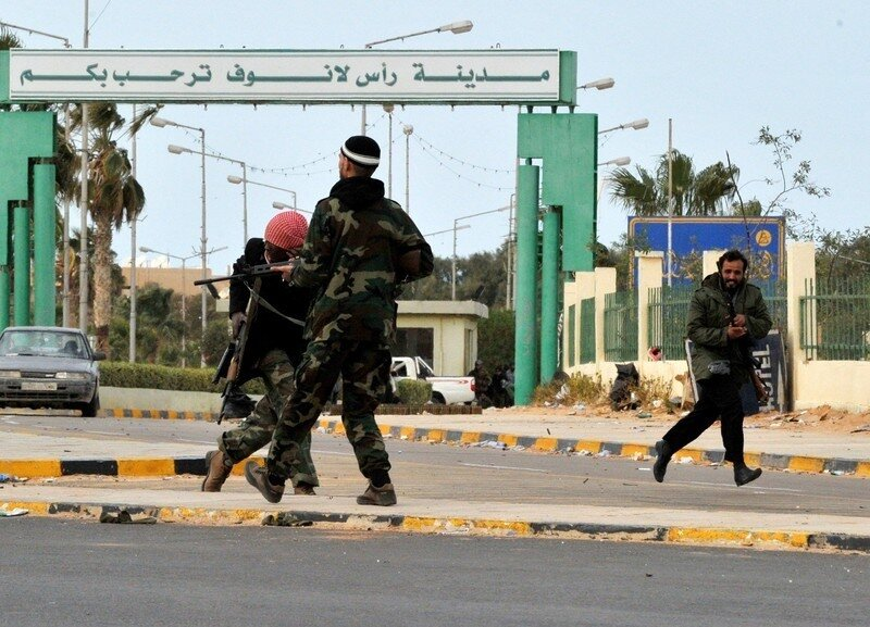 Libyan rebel fighters run for cover as t