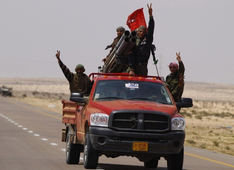 Rebel fighters celebrate after firing rockets in the desert to the east of Brega, in Libya