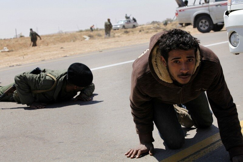 Rebels take cover from explosions during a fight with troops loyal to Muammar Gaddafi outside Brega in eastern Libya