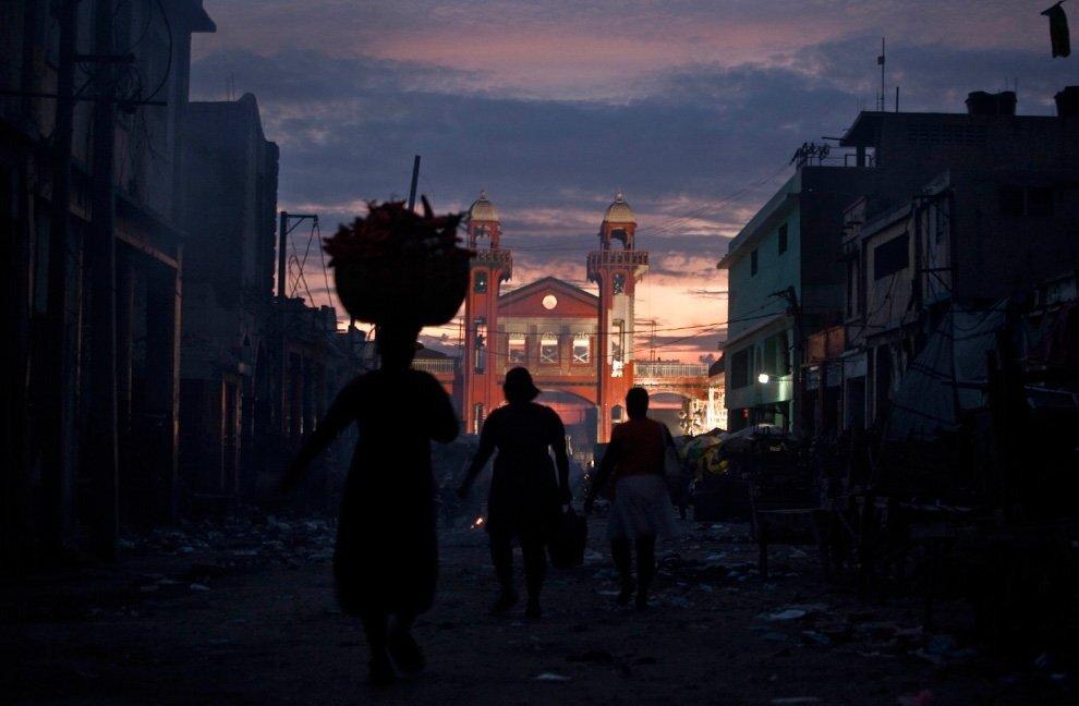 Люди идут в центре Порт-о-Пренс, на заднем плане реконструированный рынок в центре города.