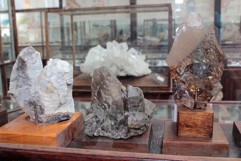 Сросток сталактитоподобных кристаллов кальцита в опаловой рубашке; скрученный многоглавый кристалл дымчатого кварца; постепенный переход дымчатого горного хрусталя в бесцветный