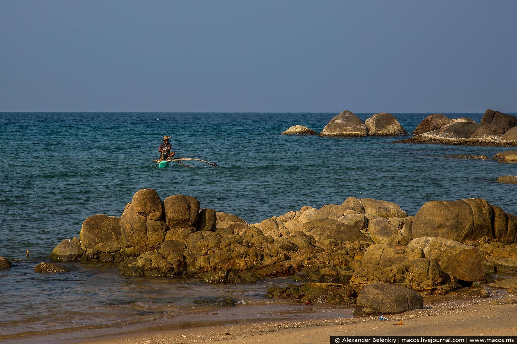 взрослая позирует на камнях на берегу моря